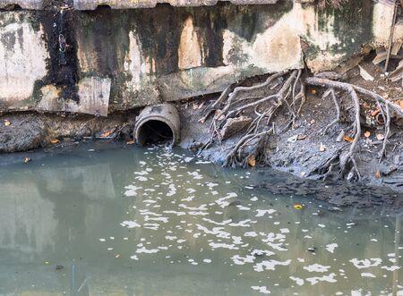 drain: Water drain via drain pipe into canal Stock Photo