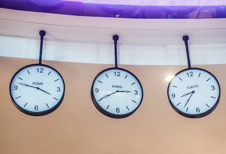 timezone: Three different international hanging wall clock, Tokyo, Paris, Rome Stock Photo