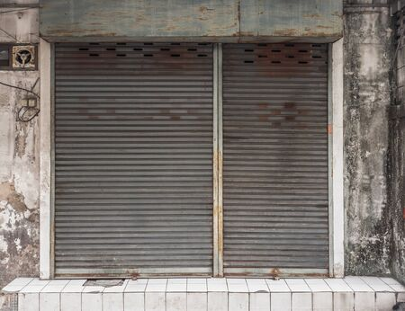 rolling garage door: In front of old building with a rusty roller shutter door Stock Photo