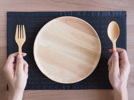 grasp: Empty wooden plate with wooden spoons and forks in the hands on woven placemat