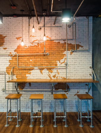 Table counter Bar with Chairs and Lights bulb over Brick wall background