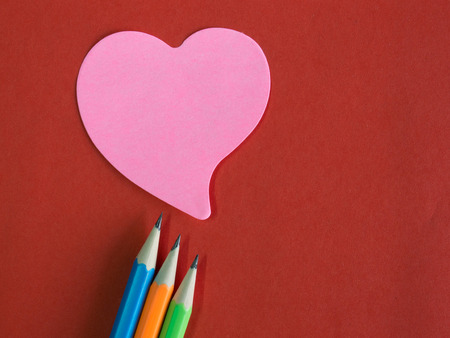 memorandum: Pink heart-shaped memorandum on red paper with colorful pencils (remember meaning of love) Stock Photo