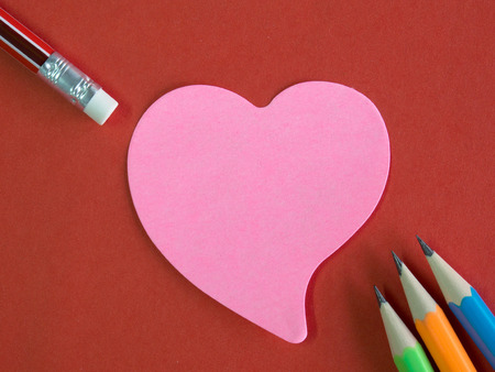memorandum: Pink heart-shaped memorandum on red paper with colorful pencils and eraser (meaning of love, remember and forgiveness)