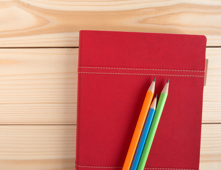 memoir: Colorful pencils put on red diary book on the wooden desk with copy space Stock Photo