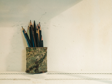 pencil holder: Used pencils in pencil holder against concrete wall background with copy space