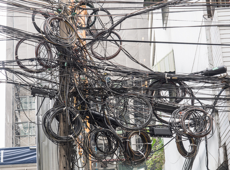 cable tangle: Messy wire and cable on electricity post near with construction site Stock Photo