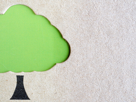 diecut: Tree shaped die-cut on brown recycled card stock with green background (environmentally friendly concept)