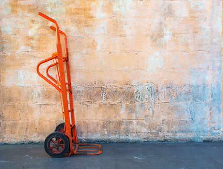 dolly: Red steel hand trolley (dolly) or sack truck against orange brick wall Stock Photo