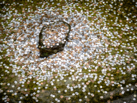 wishing: Japanese coin was thrown by traveller into wishing well in Kyoto, Japan (selective focus)