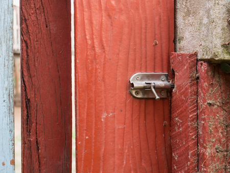 door bolt: Stainless steel bolt on the red wooden door, selective focus on bolt