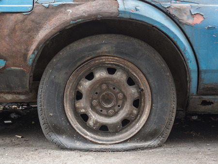 flat tire: Close up flat tire of old car park on the street waiting for repair