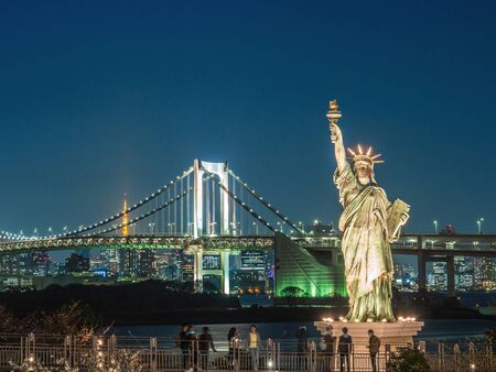 ODAIBA, TOKYO, JAPAN - MARCH 30, Replica of the Statue of Liberty at Tokyo Bay scenic point overlooking the Rainbow Bridge and Tokyo Tower. The Tokyo Bay scenic point at Odaiba is a famous meeting place for young Japanese and tourists. Editoriali