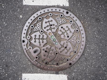 Circle steel manhole cover on asphalt street in Japan Redakční
