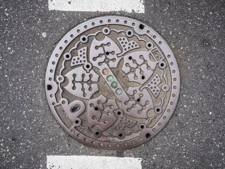 Circle steel manhole cover on asphalt street in Japan Editoriali