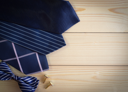 Neckties and bow and cufflinks on the wooden table with copy space