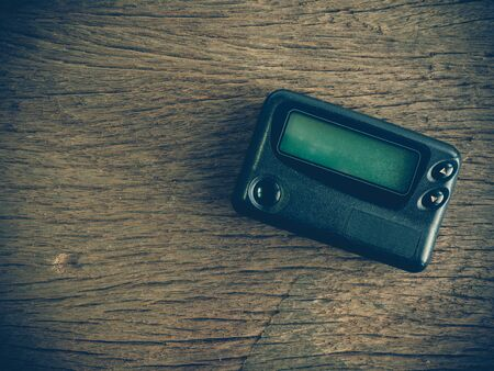 pager: Old pager device on wooden table (vintage or retro tone with lens vignetting effect)