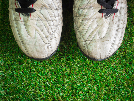 Old muddy dirty football shoes on artificial grass with copy space