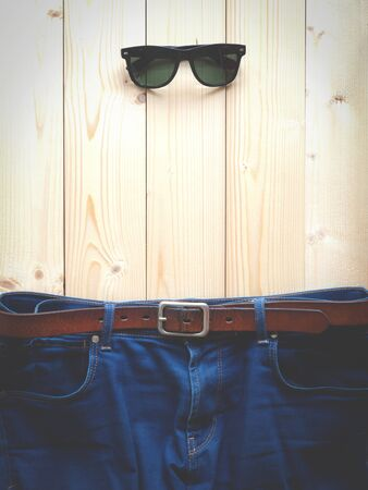 Blue jeans with brown leather belt and sunglasses on the wooden table with copy space (vintage tone)