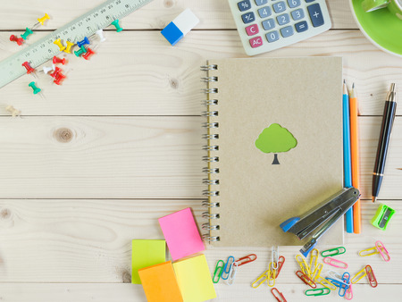 Colorful stationery and book on the wooden table with copy space