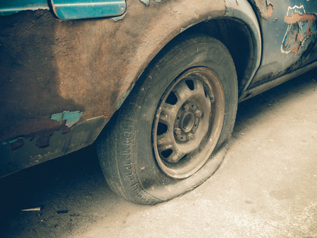 Close up flat tire of old car park on the street waiting for repair (vintage tone)
