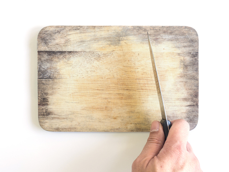 Old wooden chopping block (board) for butcher and knife in hand on white background Archivio Fotografico