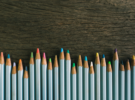 Colorful pencils arrange on the wooden table with copy space (vintage tone)