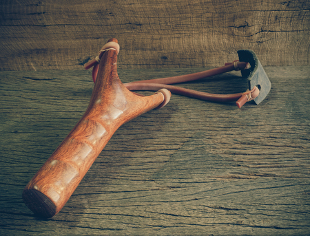 Thai wooden slingshot or catapult on the wooden table with copy space (vintage tone)