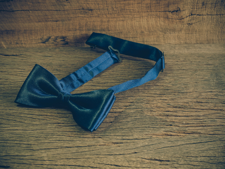 Dark blue bow tie on the wooden table with copy space (vintage tone) Archivio Fotografico