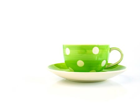 Green coffee cup with dot pattern and saucer isolated on white background Archivio Fotografico