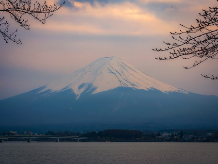 Mount Fuji at Kawaguchiko lake in Japan at sunset scene with fog and blurry foreground of branch of tree (warm tone, selective and soft focus)