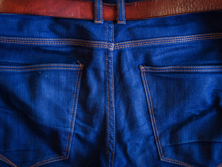 Top view of backside of blue jeans with brown leather belt