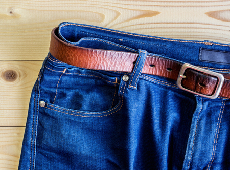 Blue jeans with brown leather belt on the wooden table