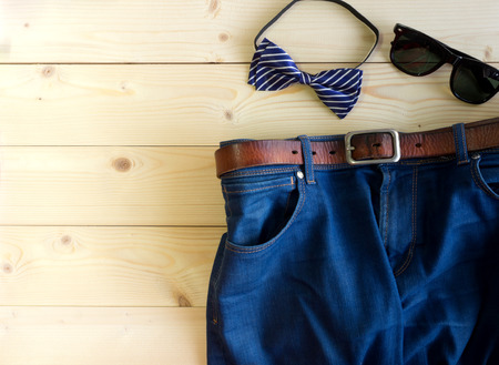 Blue jeans with brown leather belt and sunglasses and bow on the wooden table with copy space
