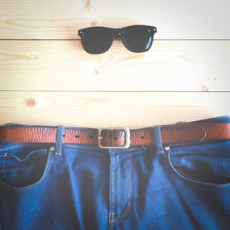 Blue jeans with brown leather belt and sunglasses on the wooden table with copy space (vintage tone and square shape) Archivio Fotografico