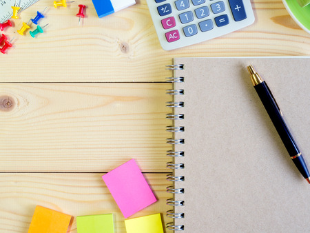 Blank book and colorful stationery on the wooden table with copy space