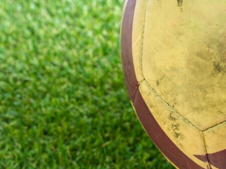Close up part of old muddy dirty football on artificial grass background with copy space (selective focus)