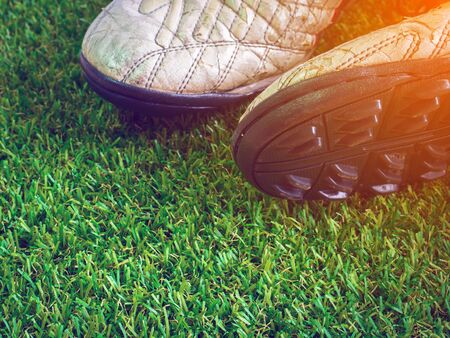 football shoes: Old muddy dirty football shoes on artificial grass with copy space (selective focus on head of shoe, vintage and warm tone) Stock Photo