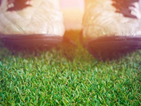 Kunstgras met onscherpe achtergrond van oude modderige vuile voetbalschoenen met exemplaarruimte (selectieve nadruk op kunstmatig gras en warme toon)