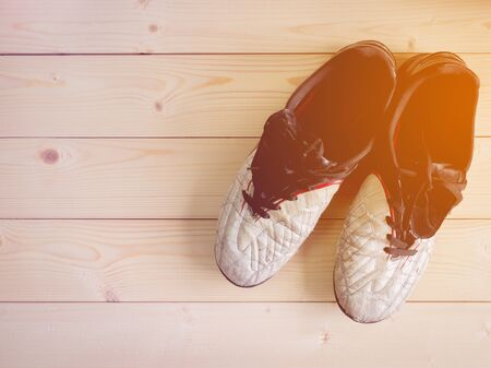 dirty football: Old dirty football shoes on the wooden table with copy space (vintage and warm tone)