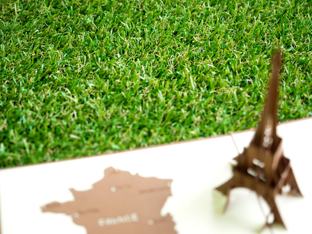 Artificial grass with blurry foreground of Eiffel tower Archivio Fotografico