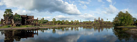 Panorama of Angkor Wat complex, Library building, Palm trees and their reflection one the pond against cloudy blue sky
