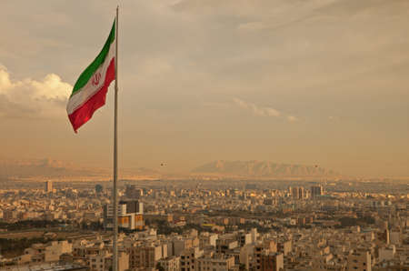 Iran flag waving  in the wind above skyline of Tehran lit by orange glow of sunset  Stock fotó