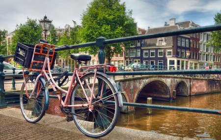 Amsterdam canal scene with a pink bicycle and brick bridges  photo