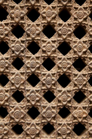 latticework: Carved stone latticework with flowers and squares design creating a perforated wall  Stock Photo