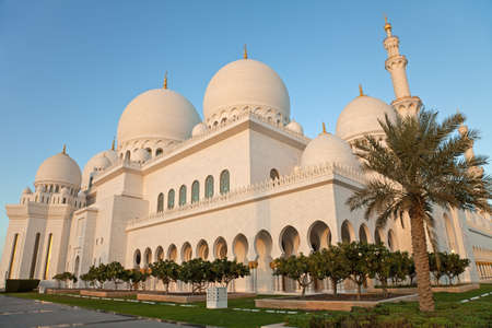 Warm orange light of sunset on white marble grand mosque of Abu Dhabi  photo