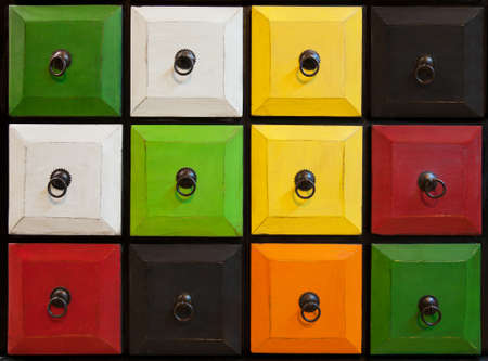 Facade of a colorful old drawer with closed square chambers