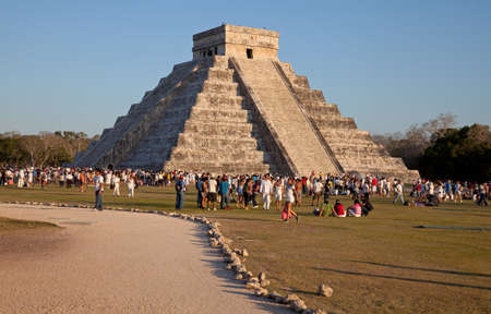 Large Group of tourists visiting the El Castillo temple during sunset in Chichen Itza, Mexico  This temple is one of the landmarks of Mexico