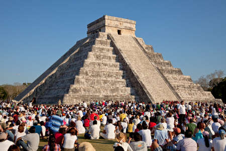Group of tourists watching the feathered serpent crawling down the temple on Equinox in Chichen Itza, Mexico  This is one of the seven wonders of world  Editorial