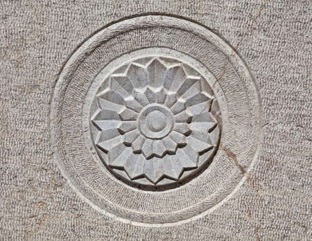 Carved lotus shaped motif on the surface of a gray stone  photo