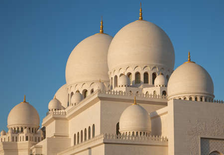 Warm orange light of sunset on white marble domes of Abu Dhabi grand mosque  photo
